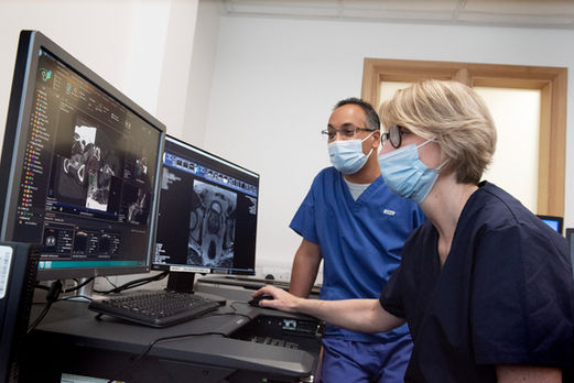 2 doctors looking at scans on screens in hospital