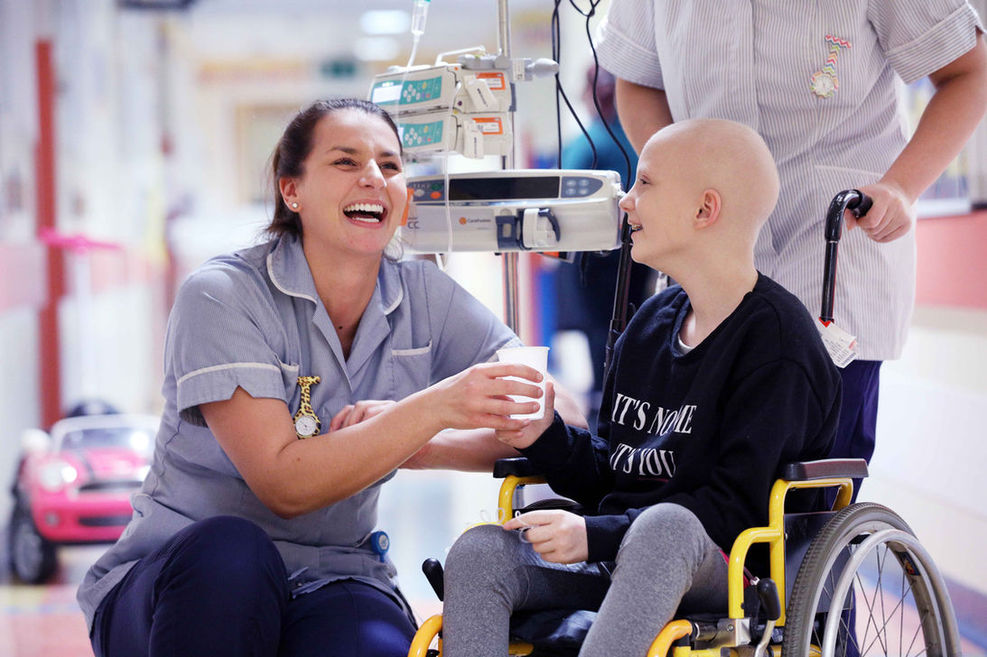 Children's-Ward-cancer-patient - in wheel chair with nurse handing her a drink