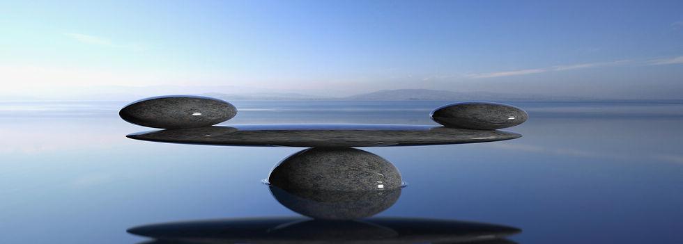 Balancing Zen stones in water with blue