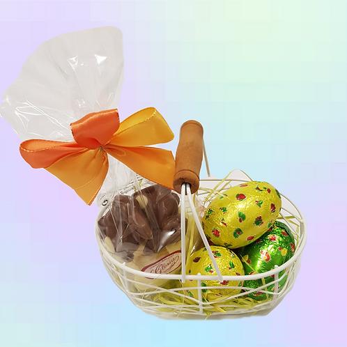 Cesta con surtido de huevos y conejos de chocolate