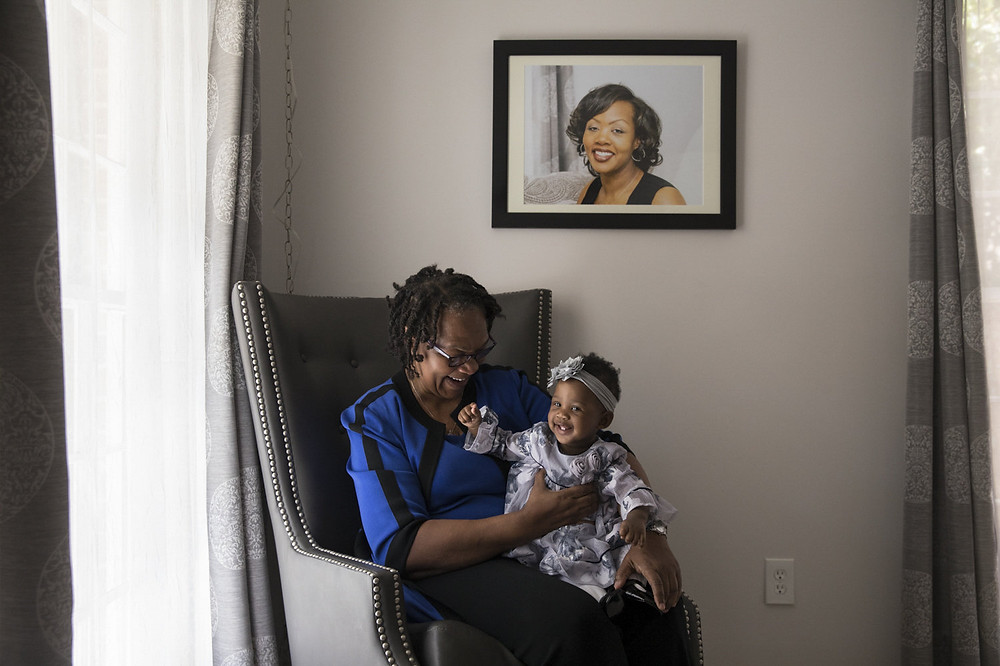 Wanda Irving holds her granddaughter, Soleil, in front of a portrait of Soleil's mother, Shalon, at her home in Sandy Springs, Ga. Wanda is raising Soleil since Shalon died of complications due to hypertension a few weeks after giving birth. Becky Harlan/NPR