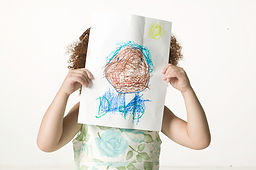 young child holding her artwork