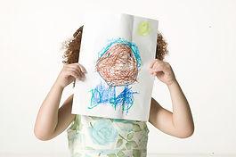 enfant qui tient un dessin devant son visage