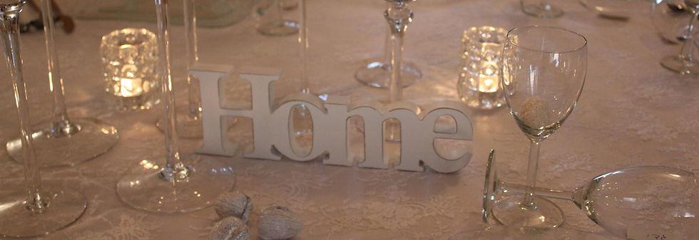 המילה HOME מעץ במרכז שולחן חג