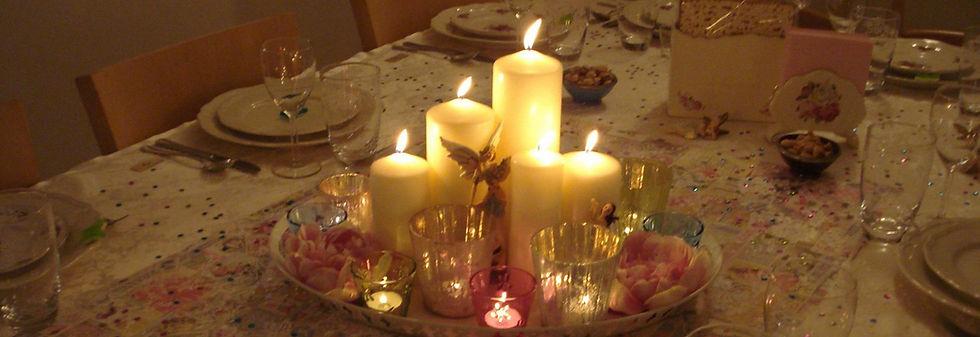 מרכז שולחן מעוצב וחגיגי עם נרות, פרחים ופיות