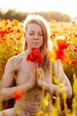 Portrait of a beautiful girl with a bouquet of poppies in her hands meditating on a poppy