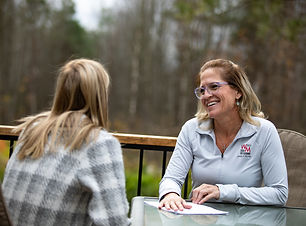 Photo of Wendy Mason smiling & coaching a lady outside.