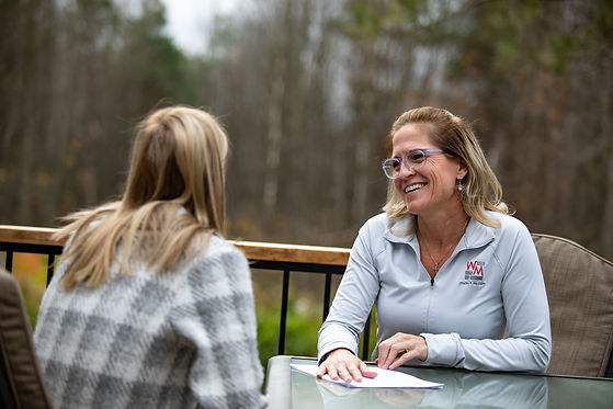 Health & Life Coach Wendy Mason consulting a client outdoors at a table.
