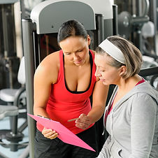 Senior woman with personal trainer looking exercise chart at gym.jpg