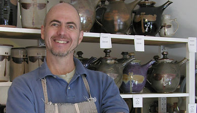 Richard Fisher stands in front of his stoneware.