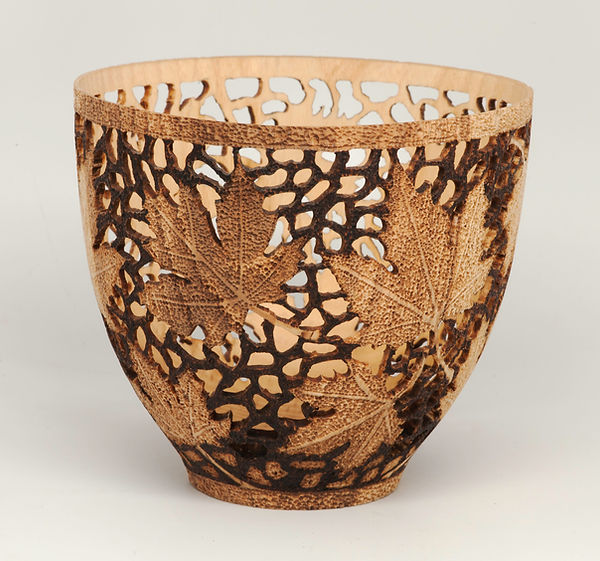An intricately designed ash vase with maple leaves.