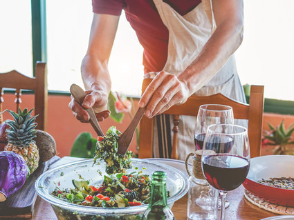 Male chef serving organic vegan salad for dinner - Cook man preparing the table for meal w