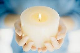 Hands holding a white candle_Publications by KT