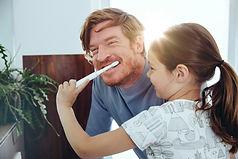 Mädchen, das die Zähne des Vaters bürstet