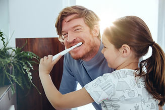 Chica cepillando los dientes de papá