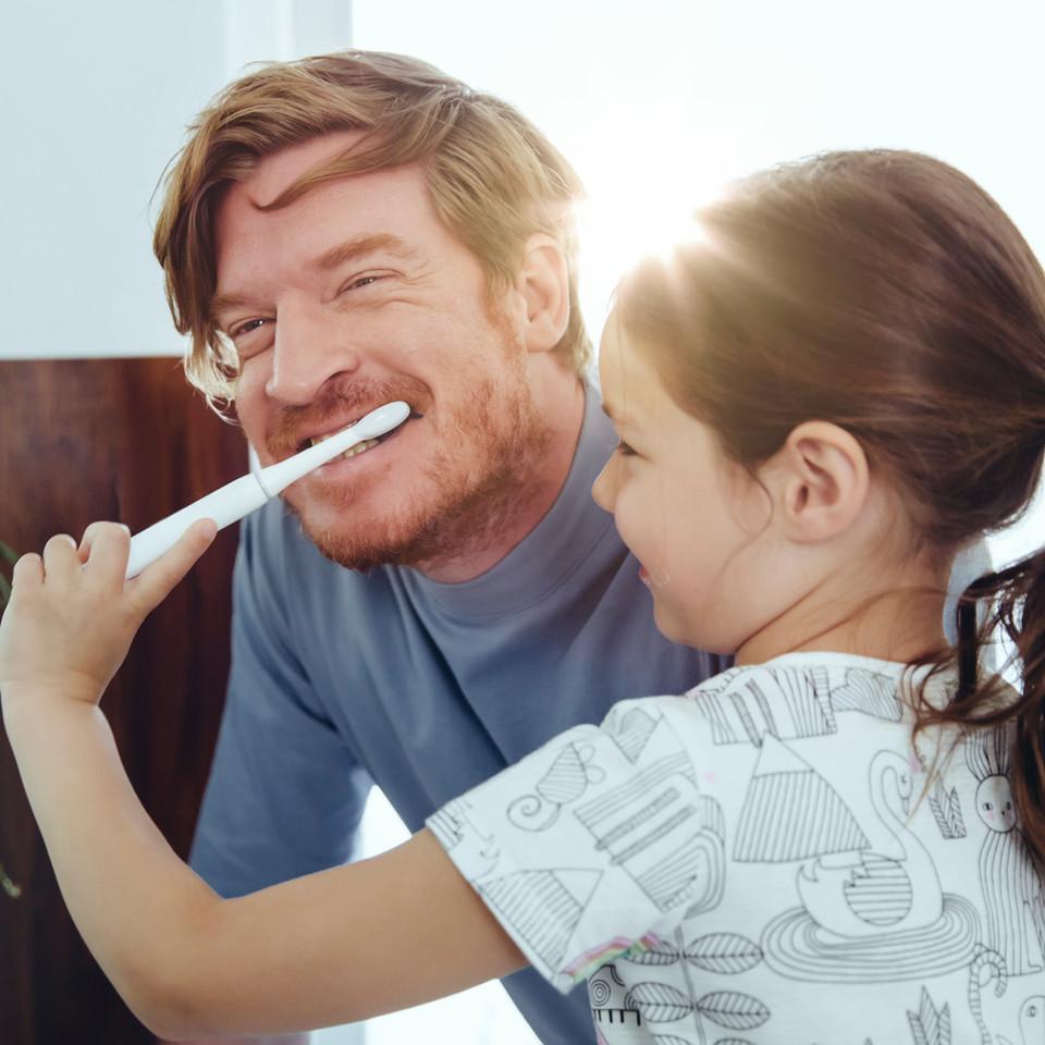 Mädchen, das die Zähne des Vaters bürste