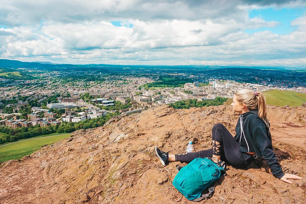 girl climbing mountain while on vacation in Edinburgh tips.