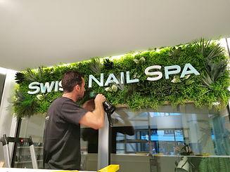 Photo lors de l'installation d'un tableau Végétal artificiel avec logo de l'entreprise réalisé par Végétal Tendance en Suisse