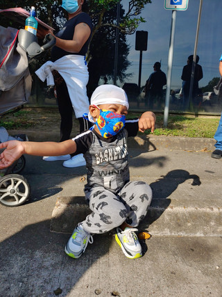 June 2020 - child waiting in line for rental assistance smiles after receiving a free spiderman mask from assistance staff