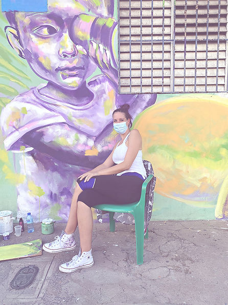 Artist Bonesy sitting on a chair in front of her mural.