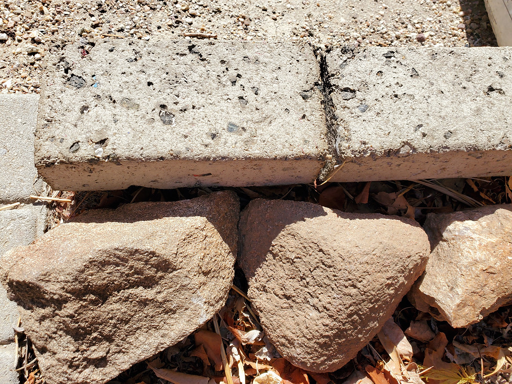 There are two paper bricks towards the top of the photo above the 3 rocks. They are a light colored brick.