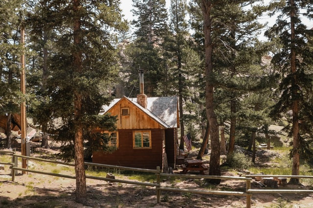 A small log cabin located in Colorado sits in a forest with wooden fencing around it. A serene scene. Humble and Quiet.