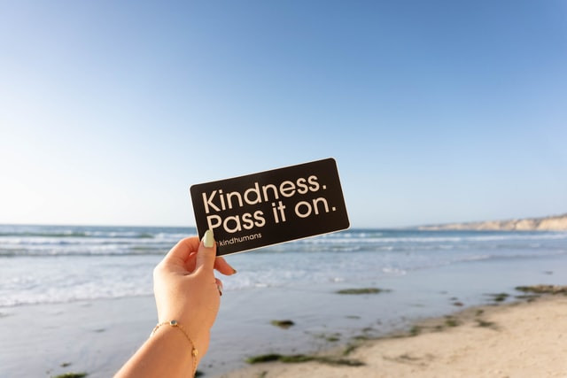 """The scene is the beach. A hand reaches out with a small sign that says, """"Kindness. Pass it on."""""""