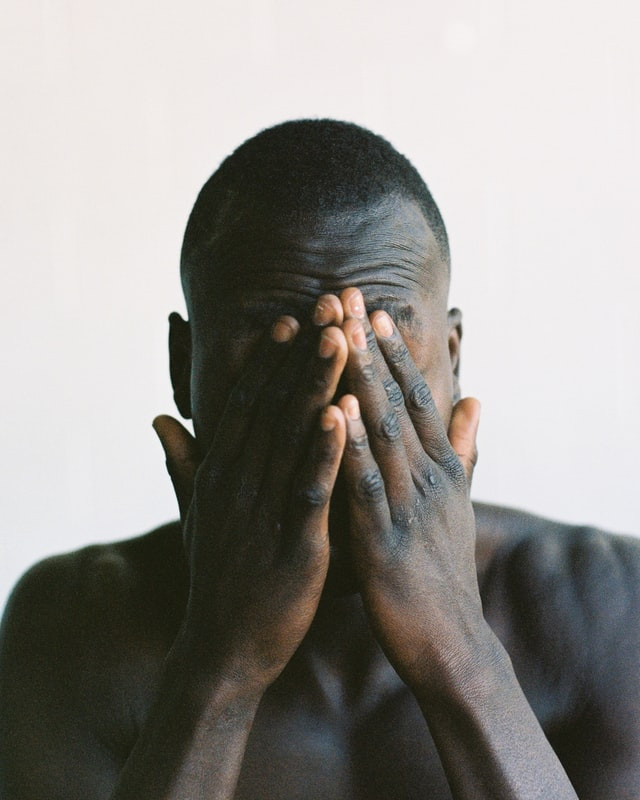 Man standing with face covered. He is exhausted. Background is white.