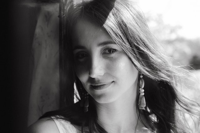 A black and white photo of a young girl leaning against a wall. She has long metal beaded earrings, long fine brown hair, and a short sleeve tank top.