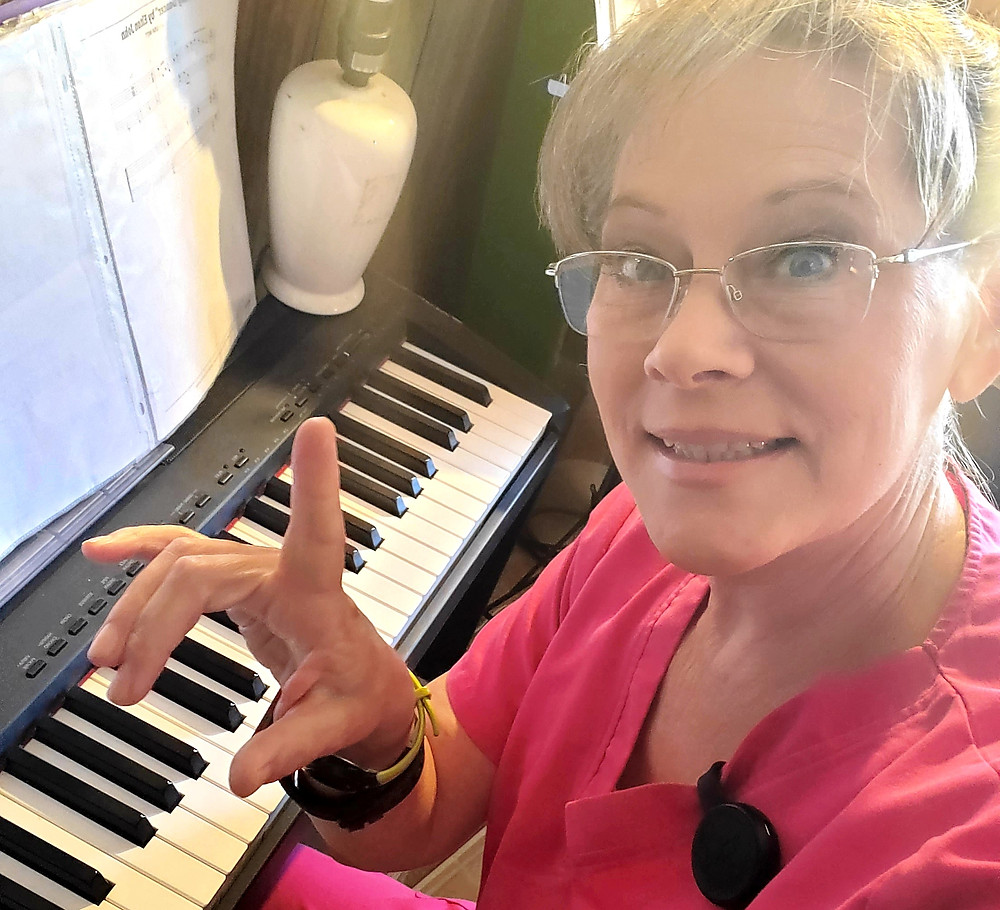 Photo of the author in her pink outfit sits at her piano at home for practice time.