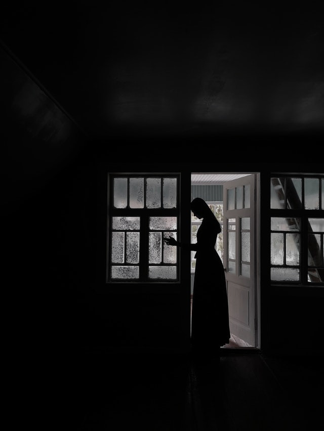 The image is darkened greatly by shadow. In the center there is a wall with many windows. It is the only light source. A young woman in a dress stands at the door. She is coming into the dark room.