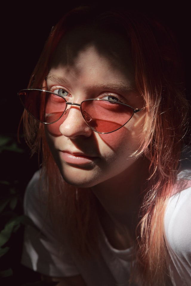 Portrait with a close up of a young woman's face. She has brownish hair falling into her face. She has a slight turn to the left. Her sunglasses are down a bit on her nose to show her hazel eyes.