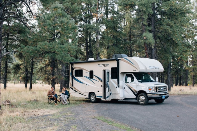 A couple are sitting in a forest enjoying the scenery. Their RV is parked right next to them.