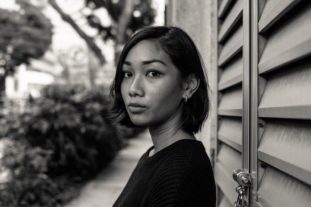 A young career woman takes a moment to look at the camera before she heads down the beautifully groomed pathway to her chosen career. A black and white photo.
