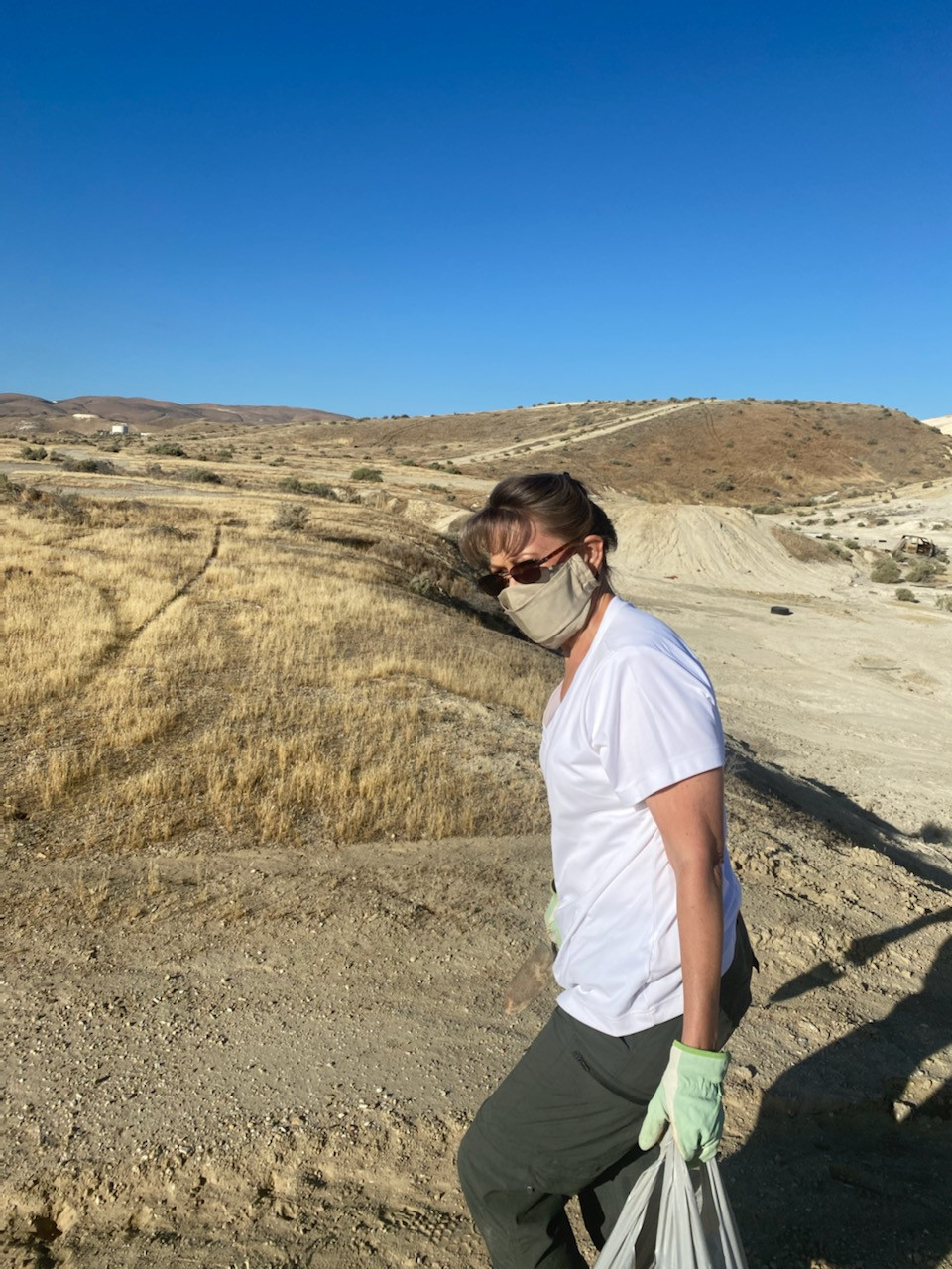 Photo of the author walking in the barren hills harvesting the clay. She has a mask on, white shirt, khaki pants, gloves, and a bag.