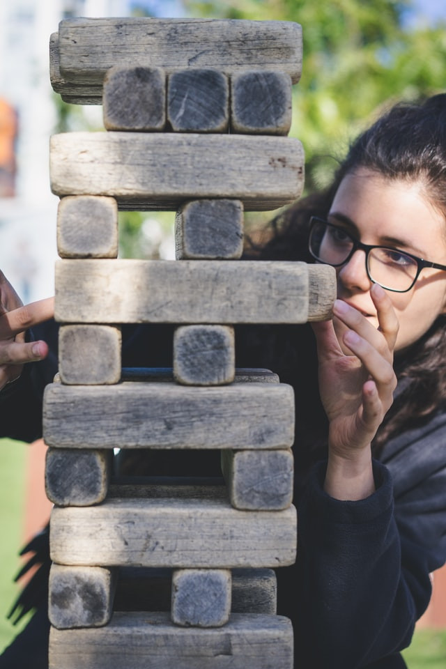 A woman is strategically pulling a wood block from an oversize Jenga game that is taller than her. She is outside. The blocks look old, warn, and splintery.