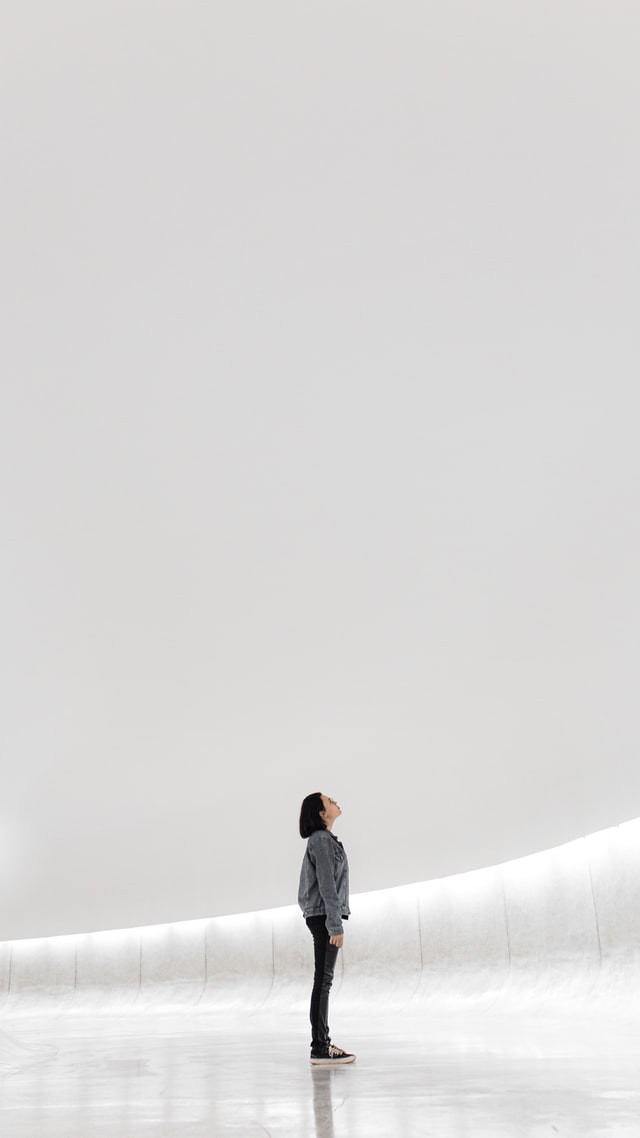 Crystal white background with a young woman standing in the center turned to her right. She is looking upward as if asking or seeking guidance.