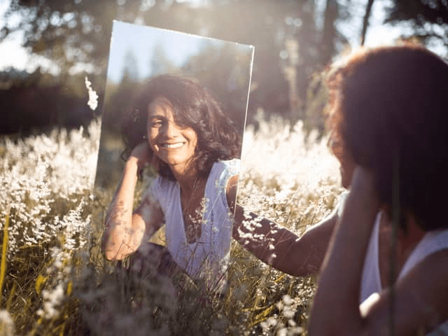 Happy, smiling woman sitting in a meadow of tall dry wild grass looking into a mirror.