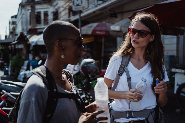 Two ladies walk and talk together while drinking bottled water. They are outside walking along a sidewalk down a busy shopping district. They are both wearing backpacks and engaged in communication.