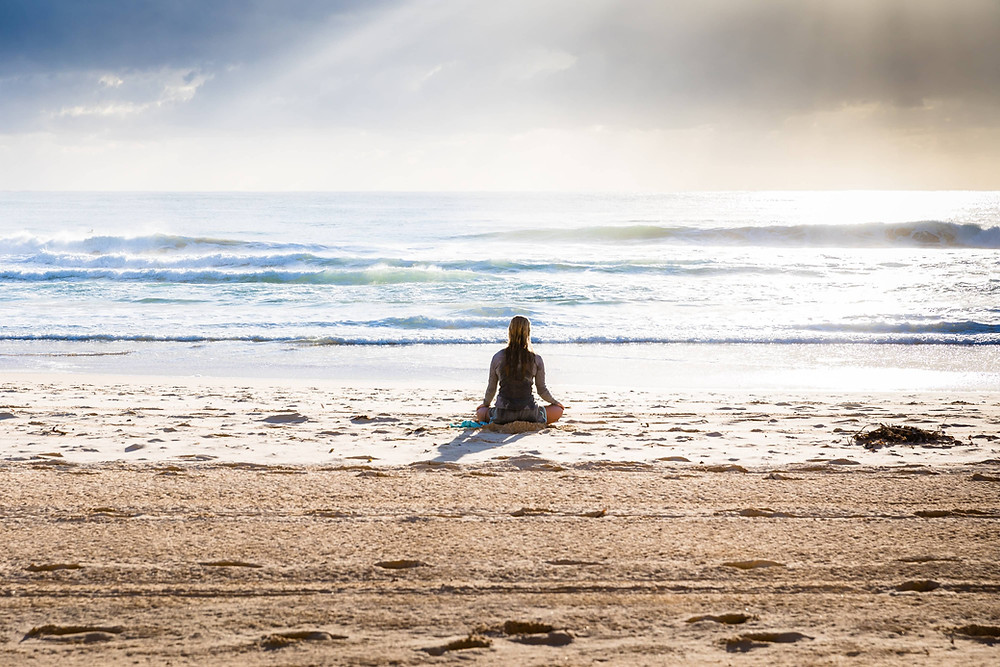 A woman sitting on the beach.