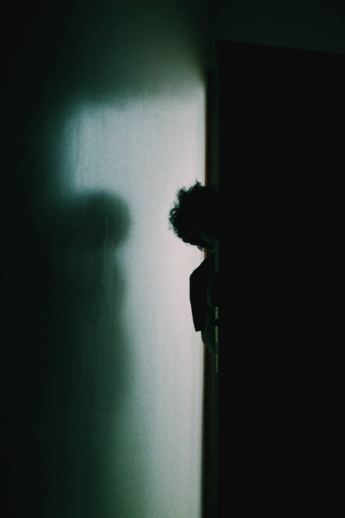 A boy in a barely lit hallway peaking around the corner into a very dark room.