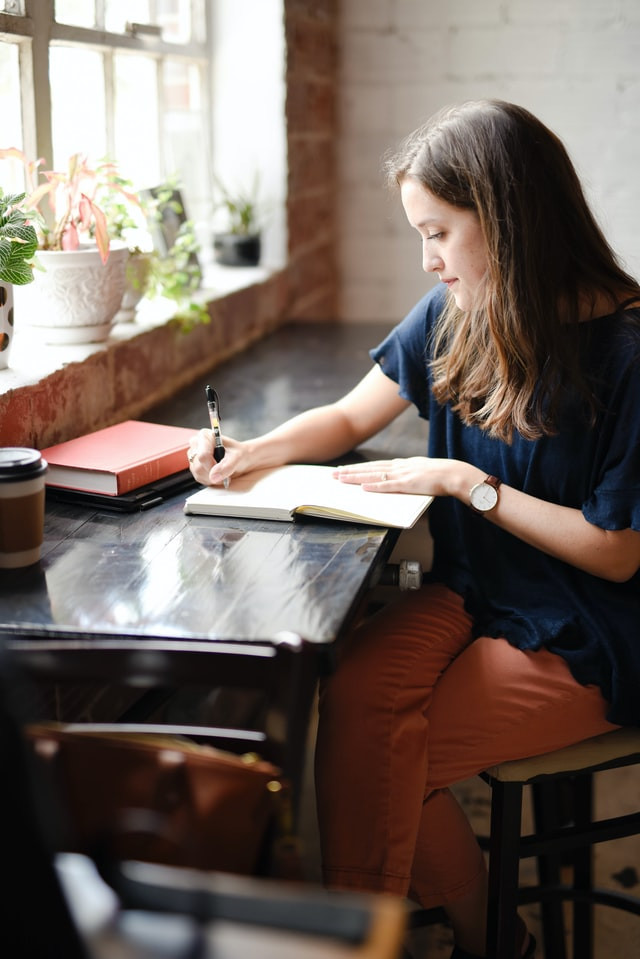 Photo of a young woman at a large dark brown table nook. She has several books. One is open and she is writing in it with a ball point pen. She has orange slacks, a blue dress shirt, and long brown hair.