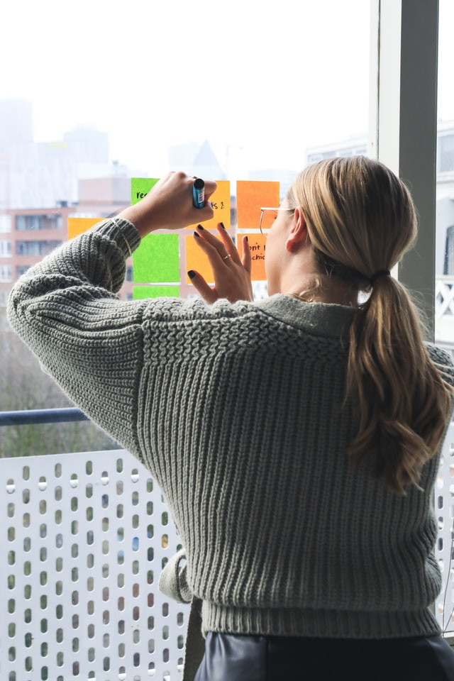 A woman with a pony tail is facing her large window. There are an assorted colors arranged on the window in a planning goals style. With a black marker she is writing a plan for herself.