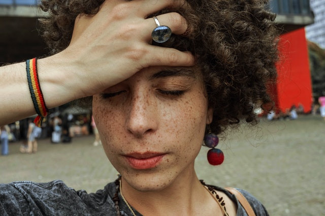A woman stands outside of a shopping area. Her hand is holding her forehead. Her eyes are closed. She looks like she is anxious and overwhelmed but with a subdued face. Her hair is short with tight curls all over her head. She is beautifully freckle faced. She has a rainbow color wrist band and bright red bangles at her ears.