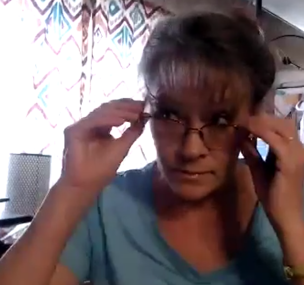 Bobbi busy thinking at her desk. Both of her hands are pulling her glasses downward.