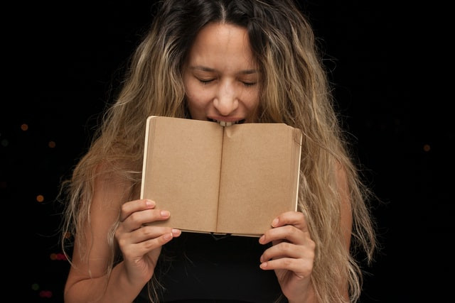 Photo Description: A young woman with long wavy brown hair and a black tank top angrily bites down on a book as if she is trying to keep herself from making a bad decision in anger.