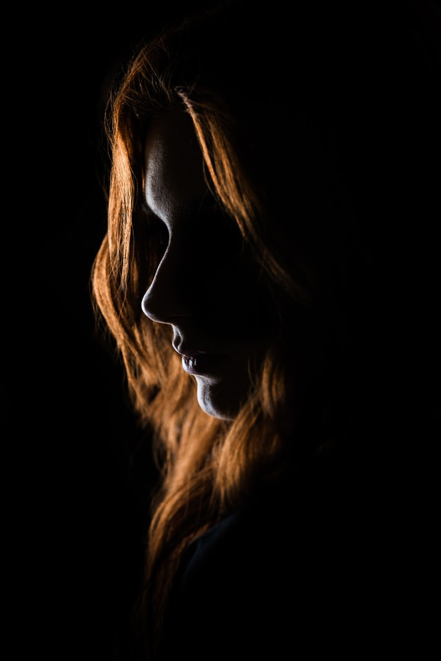 Silhouette of a woman face. You can see clearly she has red hair.
