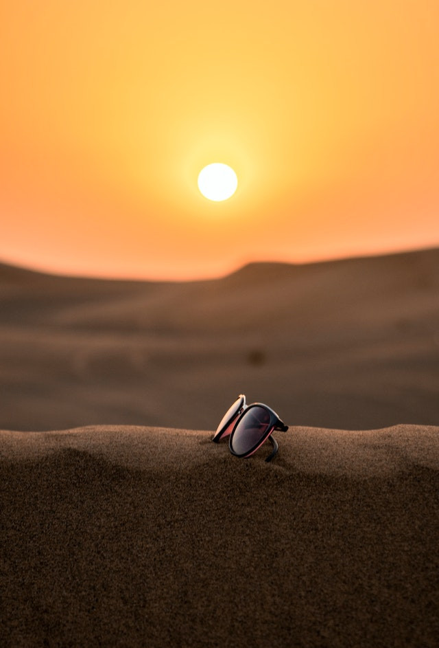 Photo Description: The center of the photo is a pair of sunglasses alone on a sandy hill in the middle of a desert. The sun is bright and blaring down on the sand dunes.