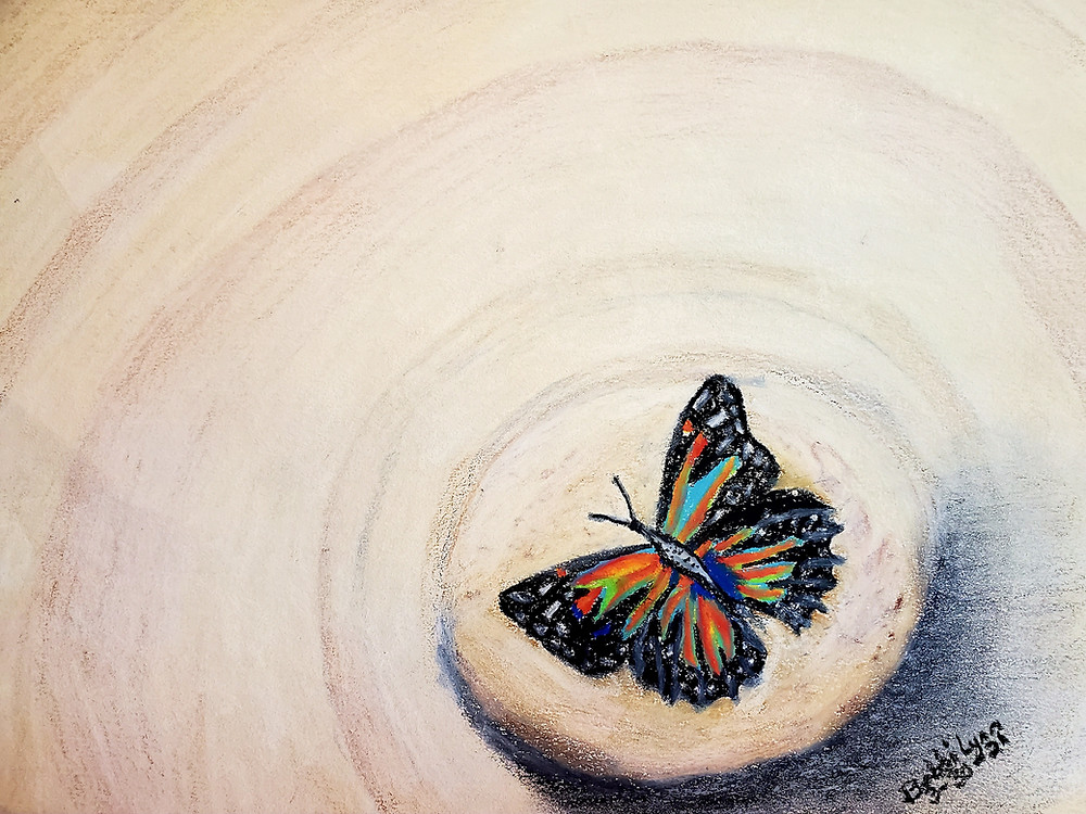 Artwork is of a colorful butterfly resting on a small lightly colored stone. The stone is resting in beach sand.