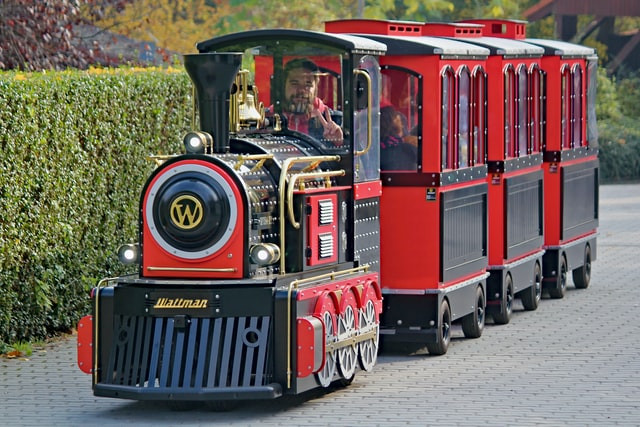 A mini train with the brand Waltman on the front grill. It has one smiling engineer driving it. It is pulling 3 mini passenger areas. It is shiny, new, and barely taller than the finely trimmed bushes bordering the brick road the train is on.